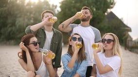 朋友获得乐趣享用饮料和放松在海滩的小组在日落在慢动作 年轻人和妇女 股票视频