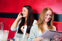 朋友获得乐趣在咖啡馆 免版税库存照片