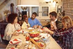 朋友获得乐趣在家庭圣诞晚餐 免版税库存照片