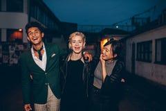年轻朋友获得在城市街道上的乐趣在晚上 库存照片