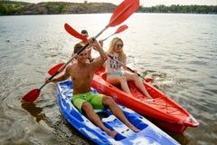 朋友获得在皮船的乐趣在美丽的河或湖在日落 免版税库存照片