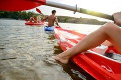 朋友获得在皮船的乐趣在美丽的河或湖在日落 免版税库存图片