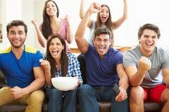 朋友观看足球庆祝目标的小组 免版税库存图片