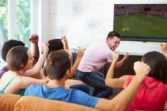 朋友观看足球庆祝目标的小组 库存图片