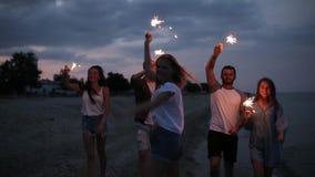 朋友走,跳舞和获得乐趣在夜党期间在与孟加拉闪烁发光物的海边在他们的手上点燃 影视素材