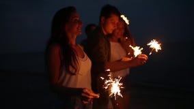 朋友走,跳舞和获得乐趣在夜党期间在与孟加拉闪烁发光物的海边在他们的手上点燃 股票录像