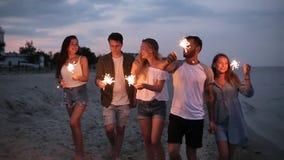 朋友走,跳舞和获得乐趣在夜党期间在与孟加拉闪烁发光物的海边在他们的手上点燃 股票视频