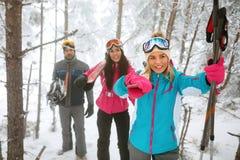 朋友通过进来在冬天森林里的挡雪板或滑雪者 免版税库存照片
