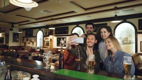 朋友采取与智能手机的selfie在酒吧 青年人摆在,笑并且谈话 啤酒瓶和 股票视频