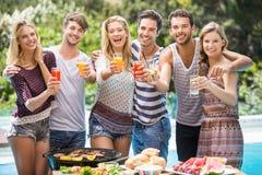 朋友画象饮用汁液在户外烤肉党 免版税图库摄影