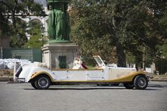 服务人的白色经典减速火箭的汽车和旅客在城市附近租赁游览 库存照片