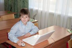 服务台他的膝上型计算机男小学生 库存图片