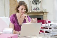 服务台她的坐使用妇女的膝上型计算&# 免版税库存图片