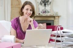 服务台她的坐使用妇女的膝上型计算&# 免版税库存照片