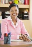 服务台她的教师年轻人 免版税库存图片