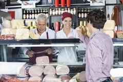 服务对顾客的微笑的女推销员在乳酪商店 免版税库存图片