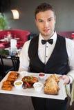 服务开胃手抓食物盛肉盘的英俊的侍者 免版税库存照片
