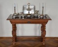 服务的古色古香的桌与银色器物 免版税库存照片
