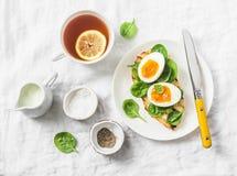 服务的复活节早午餐板材-烤面包三明治用菠菜和煮沸的鸡蛋和柠檬茶在白色背景 免版税库存图片
