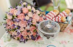 服务的桌户外 花的布置用淡紫色和玫瑰 免版税图库摄影