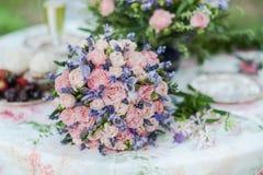 服务的桌户外 花的布置用淡紫色和玫瑰 图库摄影