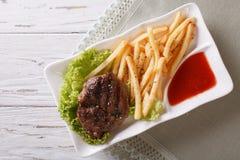 服务的烤牛排用炸薯条和调味汁 horizonta 库存照片