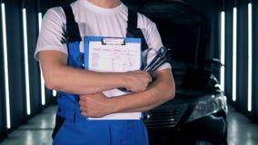 服务站和站立与剪贴板和工具的一位男性技术员 汽车服务,自动汽车修理概念 股票视频