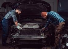 服务站 修理在车库的两位有胡子的残酷技工一辆汽车 免版税库存照片