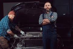 服务站 修理在车库的两位有胡子的残酷技工一辆汽车 库存照片