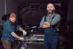 服务站 修理在车库的两位有胡子的残酷技工一辆汽车 免版税库存图片