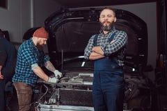 服务站 修理在车库的两位有胡子的残酷技工一辆汽车 库存图片