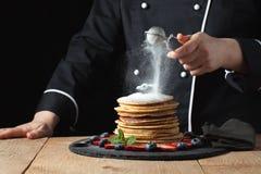 服务薄煎饼用搽粉的糖和莓果 厨师妇女手 美丽的食物静物画 有一点被定调子的图象,深黑色bac 免版税库存图片
