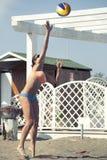 服务 妇女跳跃 背景海滩查出的排球白色 免版税库存图片