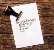 服务质量的恶劣的评估在纸的在木背景 免版税库存照片