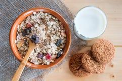 服务muesli驱散燕麦曲奇饼,在木桌上的牛奶 免版税库存照片