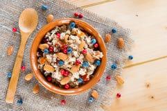 服务muesli驱散野生莓果,在木桌上的坚果 免版税库存图片