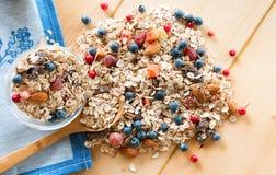服务muesli驱散野生莓果,在木桌上的坚果 免版税库存照片