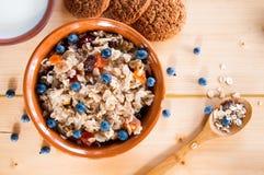 服务muesli驱散野生莓果,曲奇饼,在桌上的牛奶 库存照片