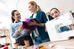 服装工厂的三个女孩 他们选择新的礼服的织品 库存照片