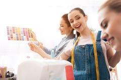 服装工厂的三个女孩 他们选择新的礼服的颜色 免版税图库摄影
