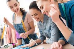 服装工厂的三个女孩 他们选择新的礼服的颜色 库存图片