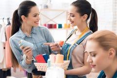 服装工厂的三个女孩 他们选择螺纹的颜色新的礼服的 库存照片