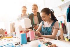 服装工厂的三名妇女 他们中的一个缝合新的礼服 免版税库存照片