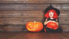 服装巫婆的愉快的儿童女孩为万圣夜用南瓜 免版税库存图片