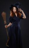 服装巫婆的美丽的红发女孩 免版税图库摄影