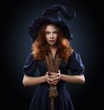 服装巫婆的美丽的红发女孩 免版税库存照片