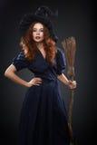 服装巫婆的美丽的红发女孩 免版税库存图片