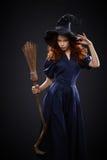 服装巫婆的美丽的红发女孩 库存照片