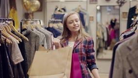 服装店的成人俏丽的妇女走到有拿着购物带来和寻找新的衣裳的机架的 股票录像