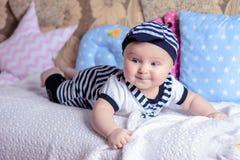 服装水手的一个美丽的小男孩在床放置在枕头附近 免版税图库摄影